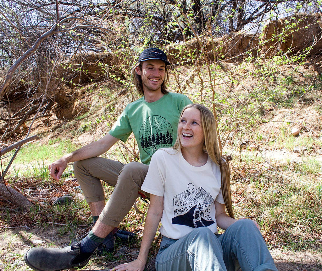 Guy and girl sitting outside wearing Honeycomb Hippie organic cotton t-shirts
