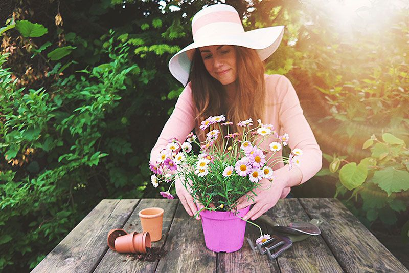 Girl planting flowers in a pot plant
