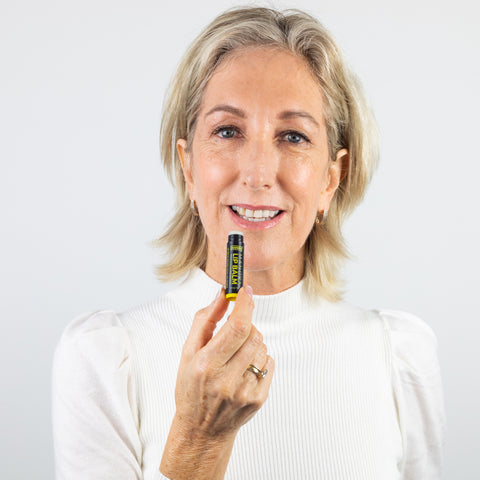 ManukaRx Mānuka Oil Lip Balm - A Mature Woman holds mānuka oil lip balm.