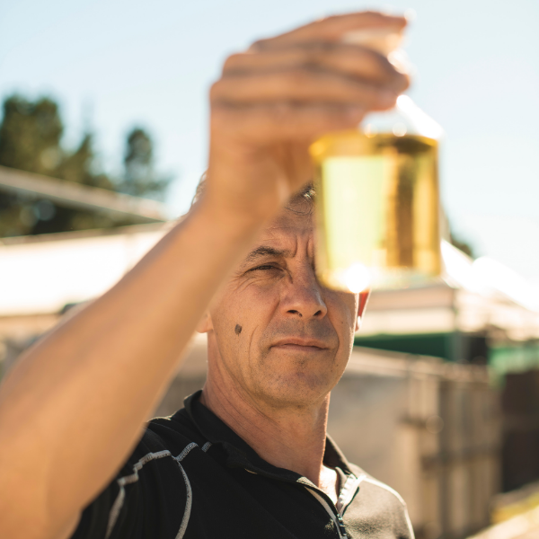 Hold the Prescription: 5 Natural Antibiotic Alternatives image showing a male holding a bottle of East Cape Manuka essential oil at a distillery.