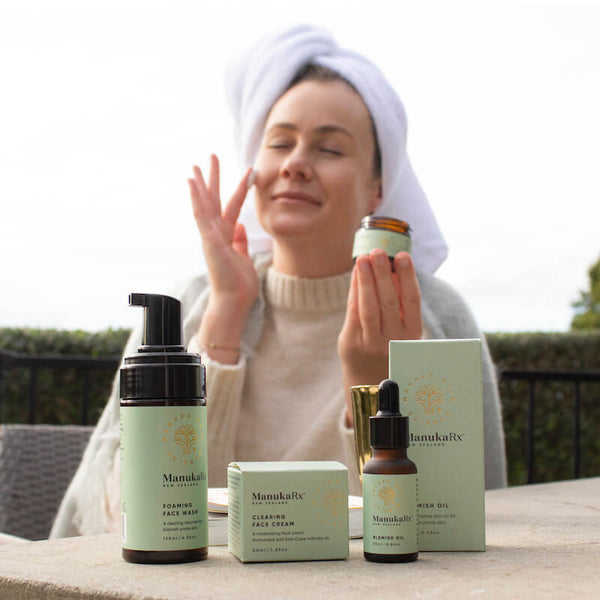 10 Most Bizarre and Bad Beauty Trends in History, and One That Is Great image showing a woman sitting outside in  a robe with beautiful skin applying ManukaRx natural skincare products made with Manuka essential oil.