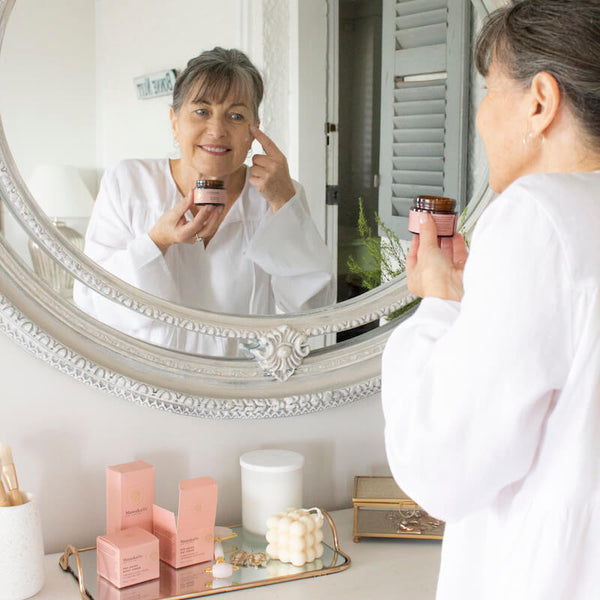 3 Incredible Skincare Products For Mature Skin blog image with an elegant mature woman applying anti-aging face cream in the mirror using ManukaRx Pro-Aging Day Cream.