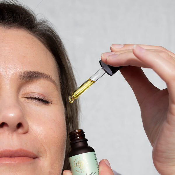 8 Surprising Mānuka Oil Uses You Might Not Know About image showing a woman with beautiful skin using Manuka Oil on her face.