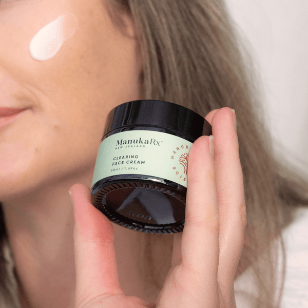 Banish Blemishes Naturally with Mānuka Oil image with ManukaRx Clearing Face Cream being used by a woman with beautiful clear skin.