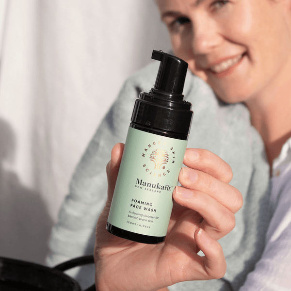 Innovative Foaming Facial Cleanse for Acne image showing ManukaRx Foaming Facial Cleanser held by a woman with beautiful clear skin.