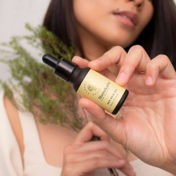 Dry Skin Solution For Accutane Users blog image featuring a woman holding ManukaRx dry skin oil and wild Manuka.