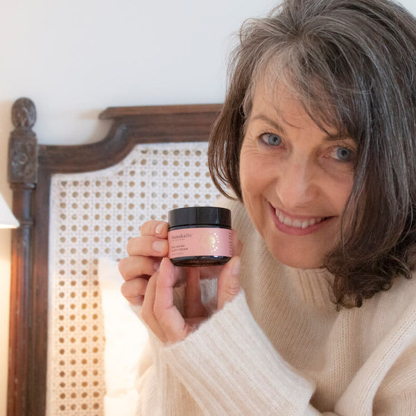 ManukaRx-East Cape Manuka Essential Oil-Spring Clean Your Skincare Routine With Mānuka Oil image showing a mature woman smiling in her bedroom holding ManukaRx Night Cream for anti-aging benefits.