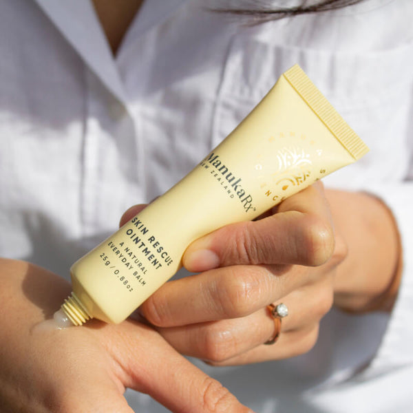 What Are The Benefits of Mānuka Essential Oil blog showing ManukaRx Manuka Skin ointment being used on a hand.