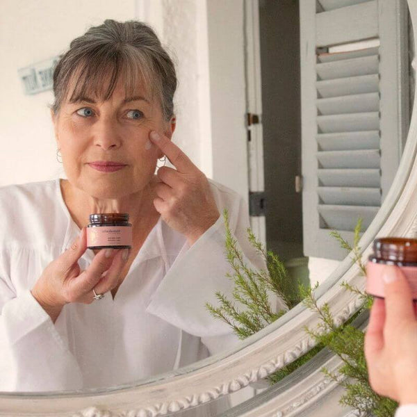 What Are The Benefits of Mānuka Essential Oil blog image showing a mature woman applying an antibacterial moisturising face cream by ManukaRx.