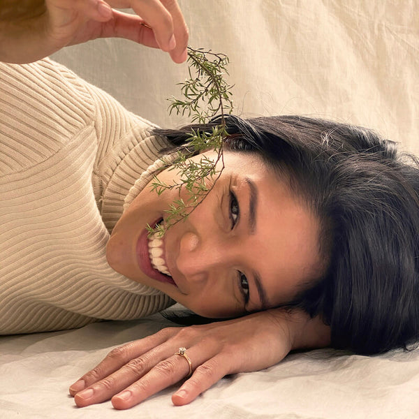 What's the Difference: Mānuka Honey vs Mānuka Essential Oil blog image showing a woman smiling and holding fresh wild Manuka plant over her face.