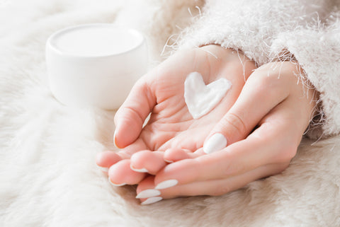 4 Ways To Use An Essential Oil Blend To Soothe Dry Skin - Dry hands with moisturiser in the shape of a heart.