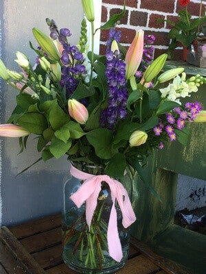 Hand tied mixed bouquet displayed in a classic recycled glass jar