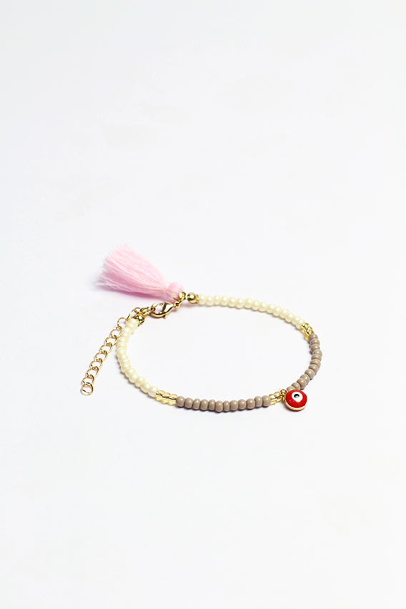 Gray/whiteآ beads bracelet with red eye pendant & pink tassel