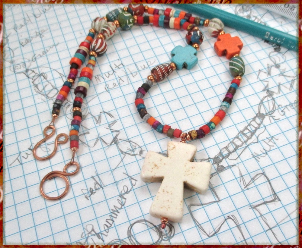 Boho style Christian necklace with large natural howlite gemstone cross pendant and multicolor strand necklace beaded with bold colorful eclectic assortment of stones, pottery, bone and copper. Handmade jewelry for religious bohemian women by Rough Magic Creations.