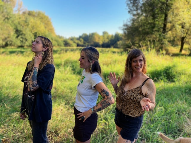 three pretty tattooed, artsy women standing in a sunny meadow on Sauvie Island outside of Portland Oregon, showing off handmade, one of a kind jewelry from Pigeon Heart Designs. Life is good. The sky is blue. People love each other. Dogs are running free