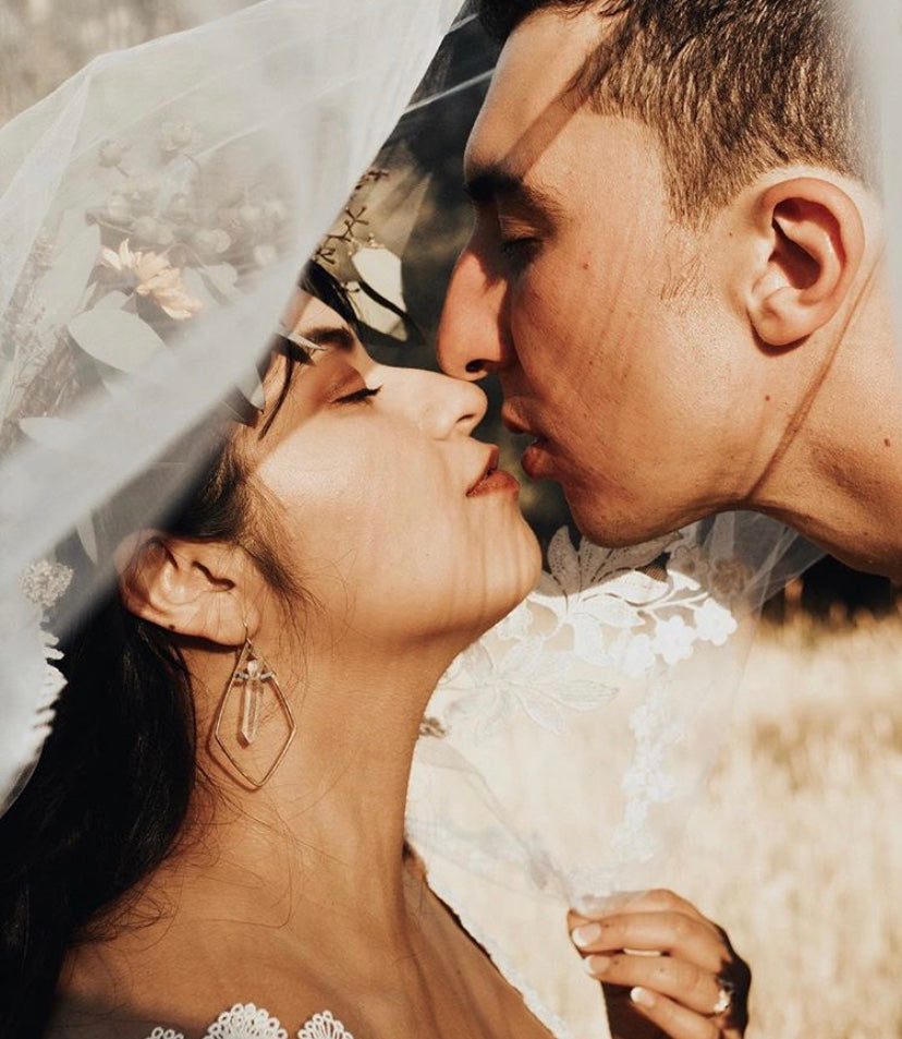 Sweet loving, newlyweds kiss. Beautiful Latino couple loving each other with woman wearing pigeon heart designs earrings beneath her bridal veil. We make bridal jewelry & jewelry as bridesmaid gifts & other wedding party presents.