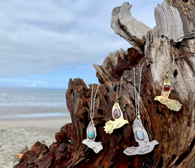 Handmade sterling and brass with gold filled chain pigeons birds with stones of turquoise, amber, Australian fire opal, ruby and many others in the shop here, on a large piece of driftwood that's agains the backdrop of the Oregon coast's  Pacific ocean