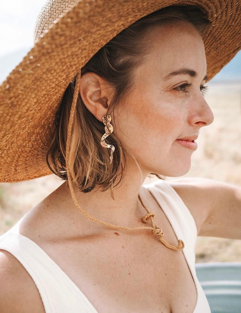 Pretty white woman modeling golden brass, handcrafted snake rattler earrings with a big sun hat, standing in a field. Great gift ideas & very versatile earrings.