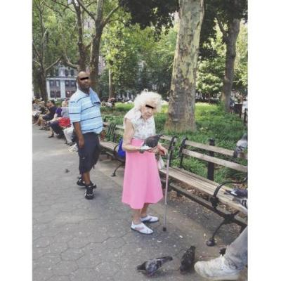 Older woman (Dorris) in Washington Square Park in NYC, amongst other Pigeon People, hanging out casually in a pink skirt with a cane, holding a resting pigeon on her arm amongst friends on the benches nearby, relaxing. It's a lovely day.