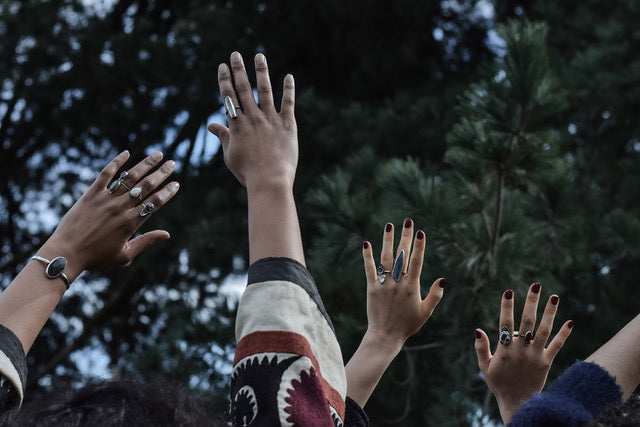 women identifying people of different shades and shapes wearing handmade, sterling silver, one of a kind rings and bracelets and reaching up towards the blue sky with green pines in the background. Looks religious but God is all around & we're spiritual.