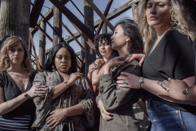 five different women standing on the banks of the Willamette River at an abandoned ship yards, modeling beautiful, handmade jewelry in a huddle.