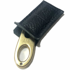 Golf divot tool solid brass with black bison leather sleeve, shown inserted.