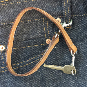 Leather key lanyard in saddle tan attached to Levis belt loop