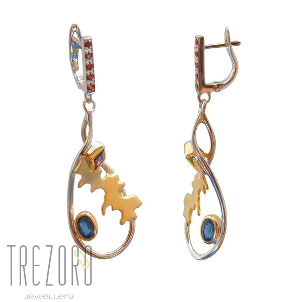 Adventure Road Designer Earrings. Sterling Silver with Garnet Sapphire. Rhodium and Gold Plated. On white.