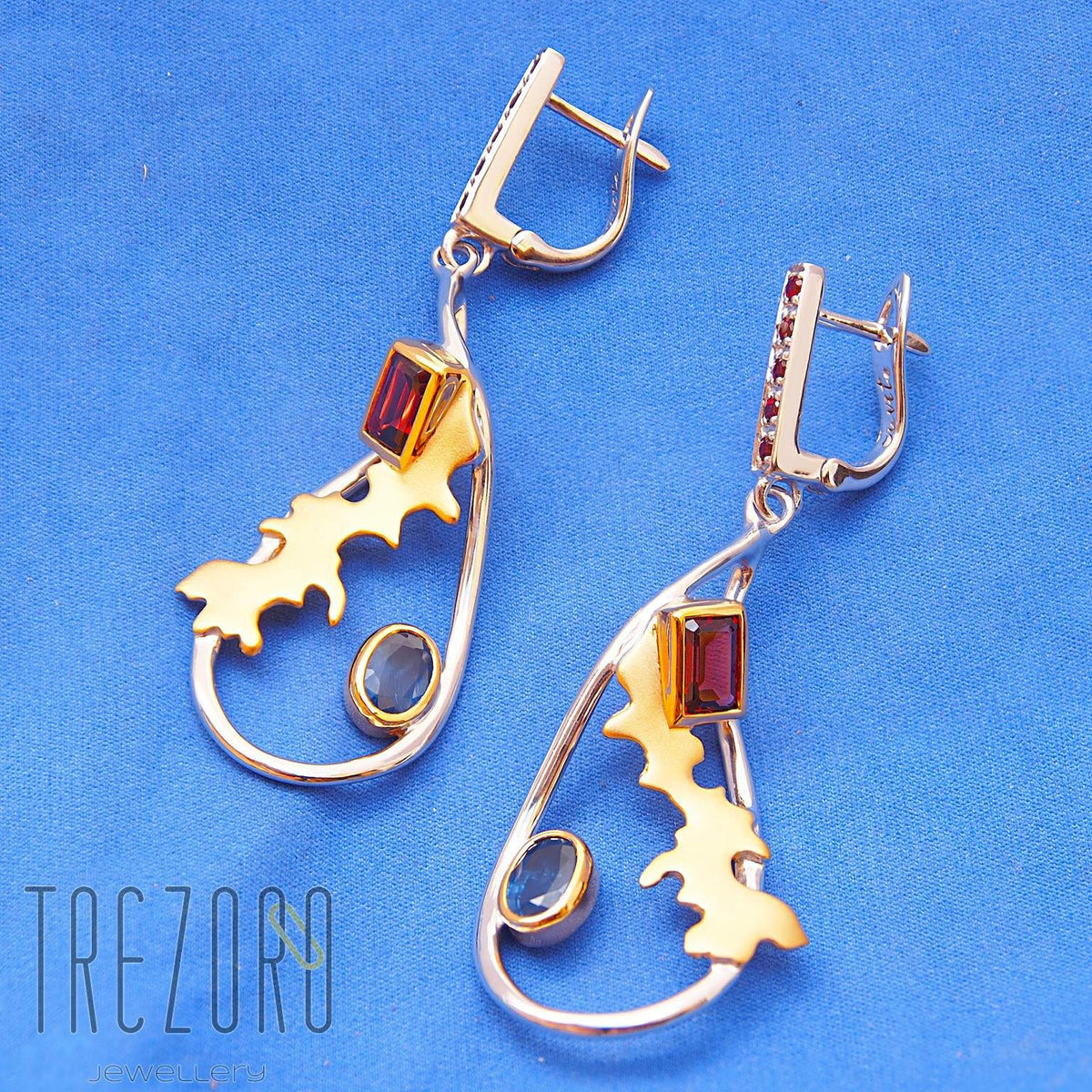 Adventure Road Designer Earrings. Sterling Silver with Garne,t Sapphire. Rhodium and Gold Plated. On blue.