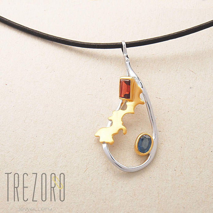 Adventure Road Designer Pendant. Sterling Silver with  Garnet and Sapphire, Rhodium and Gold Plated. On grey.