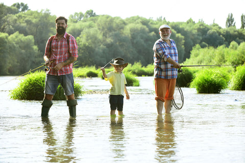 A family fishing — grandfather, father and son stood in the water with fishing rods