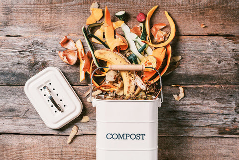 a kitchen compost caddy with food waste spilling out of it