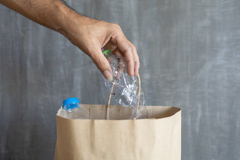 A brown paper bag being used as a bin for plastic bottles