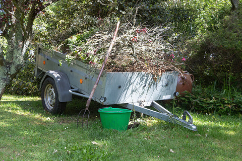A trailer full of garden waste with a pitchfork and a green bucket, located in a garden