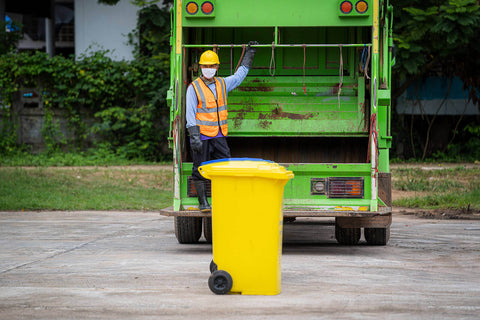 A yellow wheelie bin being collected and emptied by a man with a waste truck