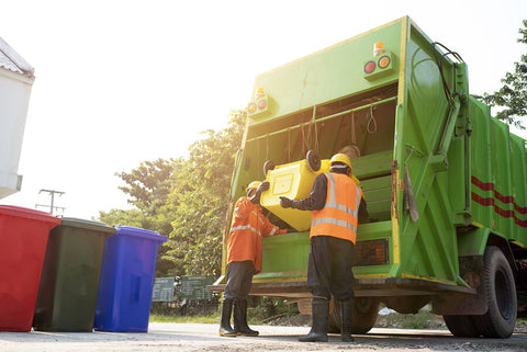 wheelie bins being emptied into a bin truck by men
