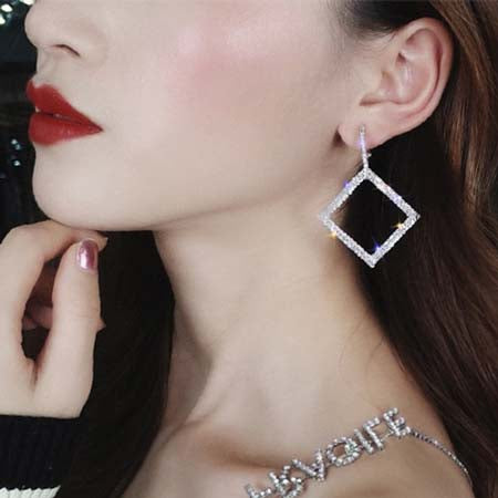 Woman-dressed-black-dress-wearing-Art-Deco-Zeus-Square-Crystal-Earrings-color-silver