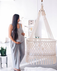 pregnant woman watching a cradle in the kids room