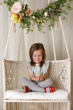 sitting baby girl watching a chick in her hands - boho style hanging chair