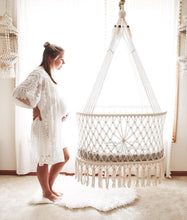 hanging cradle (hanging bassinet) in a babyroom with a pregnant mother near by