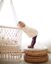 hanging cradle (hanging bassinet) in a babyroom with a kid watching the baby inside the cradle