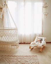 hanging cradle and a baby rocking chair near by