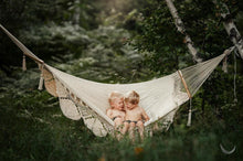 two kids on a hammock in the forest