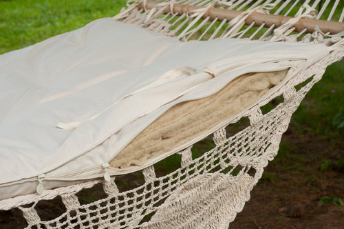 hammock with wool cushion (detailed picture). Green backyard with grass and pines