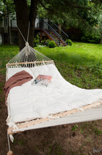 hammock with wool cushion. Green backyard with grass and pines