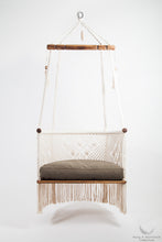 hanging chair in wood and cotton. with green cushion. studio photo. front view