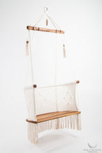 hanging chair in wood and cotton. studio photo. side view