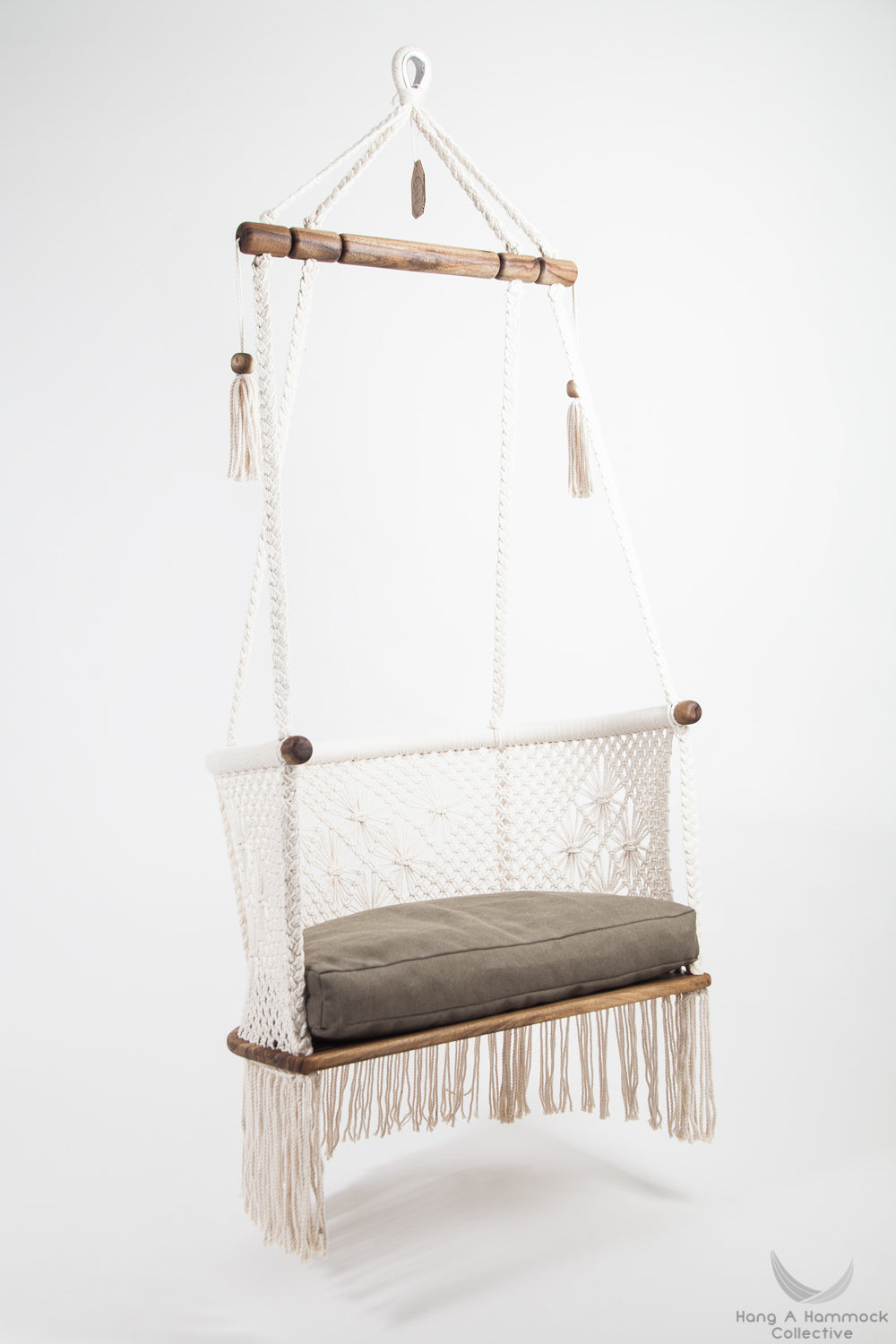 hanging chair in wood and cotton. with green cushion. studio photo. side view