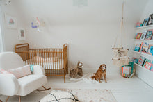 nursery with a nice dog, a armchair, a crib, a swing chair in macrame and a bookstore