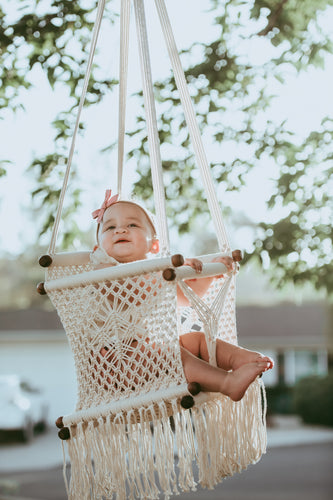 happy baby on a macrame swing chair